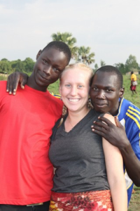 Birdsong (middle) with two of her students at the secondary school: Bonnie (red) and Emmanuel (blue). Birdsong was treating Emma for a strain in his ankle and an infection in his leg. She was also teaching them both how to treat injuries. They were both avid soccer players.